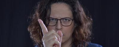 Vrouw wijst iemand met de vinger